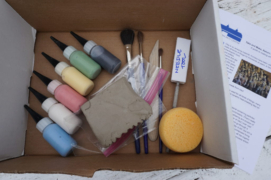 Shows the inside of a clay kit box with glaze bottles, brushes, tools, clay and instruction booklet on the side.