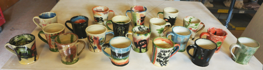 Shows a display of many completed and decorated mugs on a table in the studio.