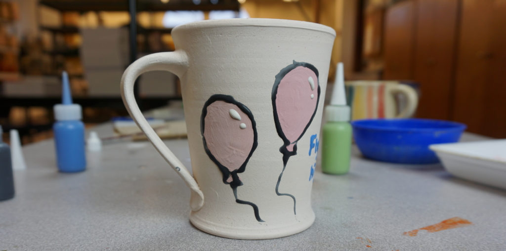 An image of a mug in the process of being decorated with a balloon design.