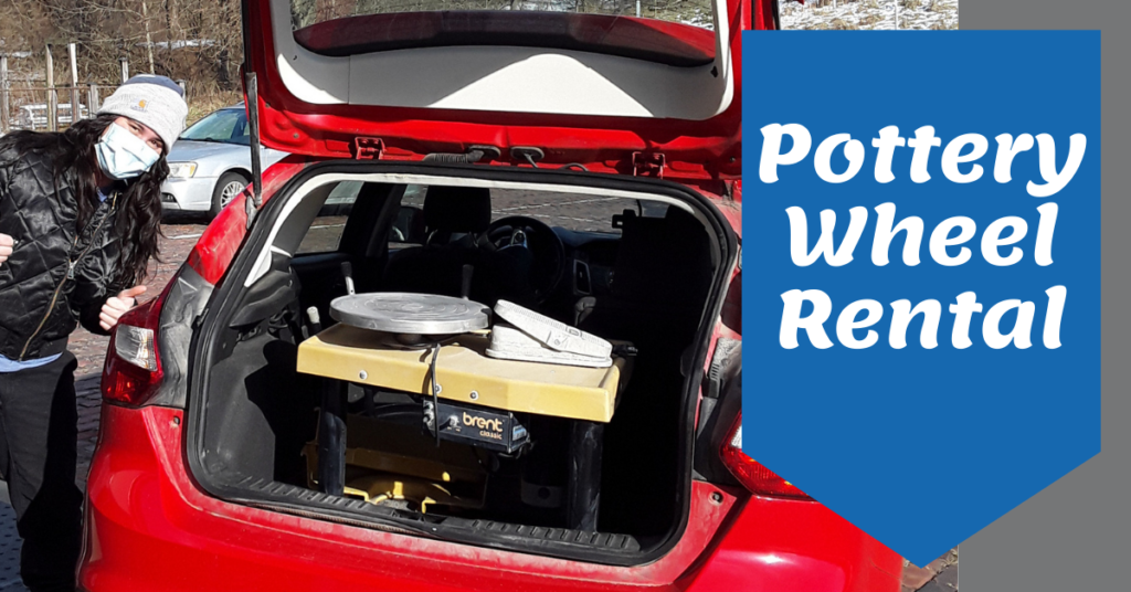 A pottery wheel is loaded in the back of a member artist's car. She is giving the thumb's up sign.