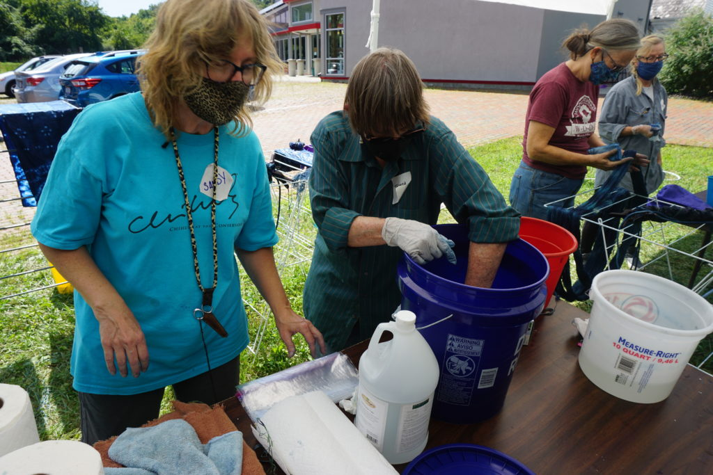 Sandy Shelenberger assisting student students with indigo dying.